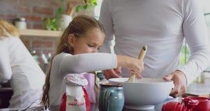 Père et fille préparant le biscuit sur le plan de travail dans la cuisine à la maison 4k banque de vidéos