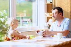 Père et fille prenant le petit déjeuner Image libre de droits