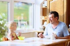 Père et fille prenant le petit déjeuner Photos libres de droits