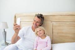 Père et fille prenant le selfie au téléphone portable dans la chambre à coucher Photos stock