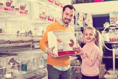 Père et fille revendiquant leur achat d'oiseau jaune canari Photographie stock libre de droits