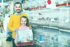 Père et fille revendiquant leur achat d'oiseau jaune canari Photo libre de droits