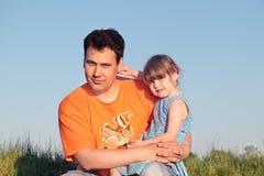 Père et fille s'asseyant dans le pré vert Images stock