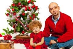 Père et fille s'asseyant près de l'arbre de Noël photographie stock