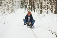 Père et fille sur le traîneau en hiver Photographie stock libre de droits