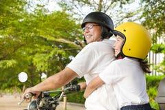 Père et fille voyageant sur la moto Images stock
