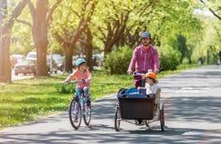 Père et filles ayant un tour avec le vélo de cargaison photos libres de droits