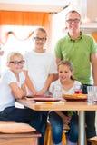 Père et filles dans la consommation de cuisine saine Images stock