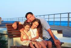 Père et filles jouant ensemble à la plage au coucher du soleil Ha Photos stock