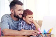 Père et fils à l'aide de l'ordinateur portable sur la table à la maison Photos stock