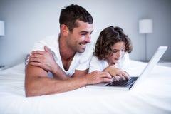 Père et fils à l'aide de l'ordinateur portable sur le lit images stock