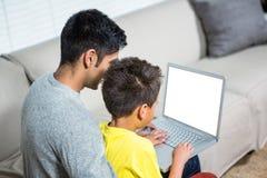 Père et fils à l'aide de l'ordinateur portable sur le sofa photo stock