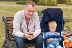 Père et fils à l'aide des smartphones tout en passant le temps ensemble dans le parc d'automne Images stock