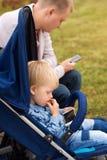 Père et fils à l'aide des smartphones tout en passant le temps ensemble dans le parc d'automne Image stock