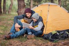 père et fils à l'aide du comprimé numérique tout en se reposant près de la tente photos stock