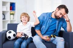 Père et fils avec des gamepads jouant le jeu vidéo à la maison Images stock