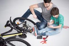 Père et fils avec des outils réparant la bicyclette ensemble sur le blanc Images stock