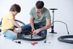 Père et fils avec des outils réparant la roue de bicyclette Image libre de droits