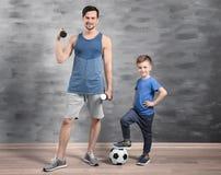 Père et fils avec du ballon de football et les haltères Image libre de droits