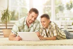 Père et fils avec l'ordinateur portable à la maison Images libres de droits