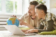 père et fils avec l'ordinateur portable et le globe Images stock
