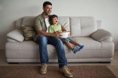 Père et fils avec le bol de maïs éclaté regardant la TV dans le salon Photographie stock