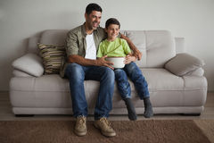 Père et fils avec le bol de maïs éclaté regardant la TV dans le salon Photographie stock libre de droits