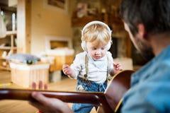 Père et fils avec le smartphone et les écouteurs, musique de écoute Images libres de droits