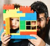 Père et fils avec les visages intéressés derrière la construction en briques colorée image stock