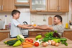 Père et fils ayant l'amusement avec des légumes dans l'intérieur à la maison de cuisine Homme et enfant Fruits et légumes Concept Photo libre de droits