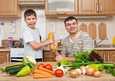 Père et fils ayant l'amusement avec des légumes dans l'intérieur à la maison de cuisine Homme et enfant Fruits et légumes Concept Images stock