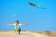 Père et fils ayant l'amusement, jouant avec le cerf-volant ensemble Images libres de droits