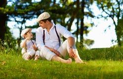Père et fils ayant l'amusement sur la pelouse de forêt Images stock