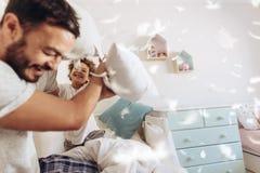 Père et fils ayant un combat d'oreiller image stock