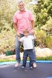 Père et fils branchant sur le tremplin dedans Photo libre de droits