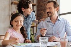 Père et fils communiquant tandis que peinture de fille Photos libres de droits