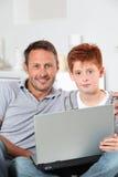 Père et fils connectés sur l'Internet Photos stock