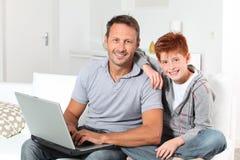 Père et fils connectés sur l'Internet Image libre de droits