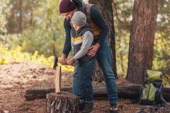 père et fils coupant le bois de chauffage images stock