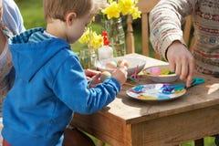Père et fils décorant des oeufs de pâques Photos stock
