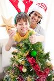 Père et fils décorant un arbre de Noël Image stock