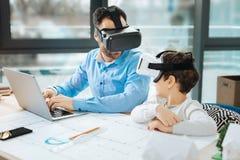 Père et fils dans des casques de VR parlant dans le bureau Images libres de droits