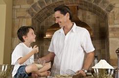 Père et fils dans la cuisine faisant cuire des biscuits de traitement au four Image libre de droits
