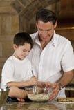 Père et fils dans la cuisine faisant cuire des biscuits de traitement au four Images libres de droits