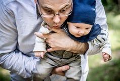 Père et fils dans la forêt regardant vers le bas Photographie stock libre de droits