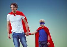 Père et fils dans le costume de super héros sur le fond bleu Photographie stock