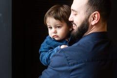 Père et fils dans les étreintes au fond noir Images libres de droits