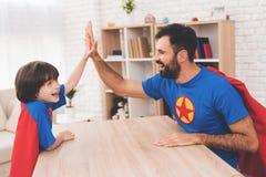 Père et fils dans les costumes des super héros Ils concurrencent dans le bras de fer Images stock