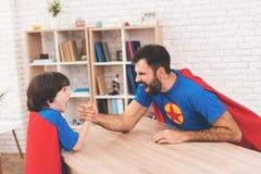 Père et fils dans les costumes des super héros Ils concurrencent dans le bras de fer Ils sont mesure leur force Photo libre de droits