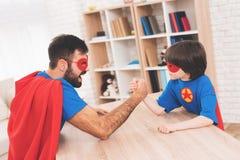 Père et fils dans les costumes des super héros Ils concurrencent dans le bras de fer Ils sont mesure leur force Photographie stock libre de droits